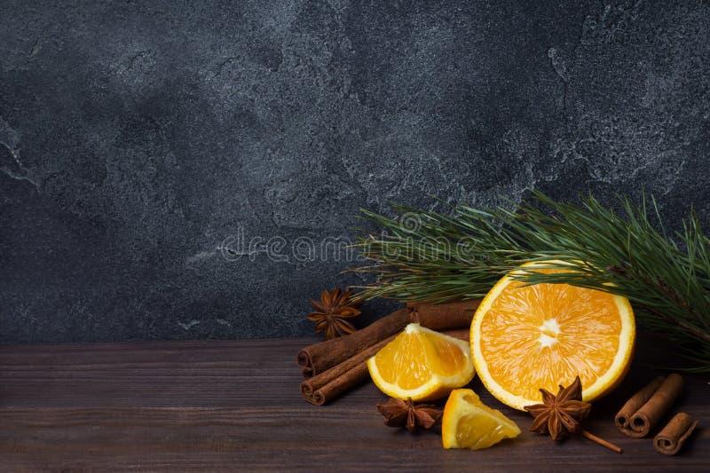 Julbegrepp med kanelbruna nya apelsiner och granfilialer på en mörk bakgrund med kopieringsutrymme arkivfoto