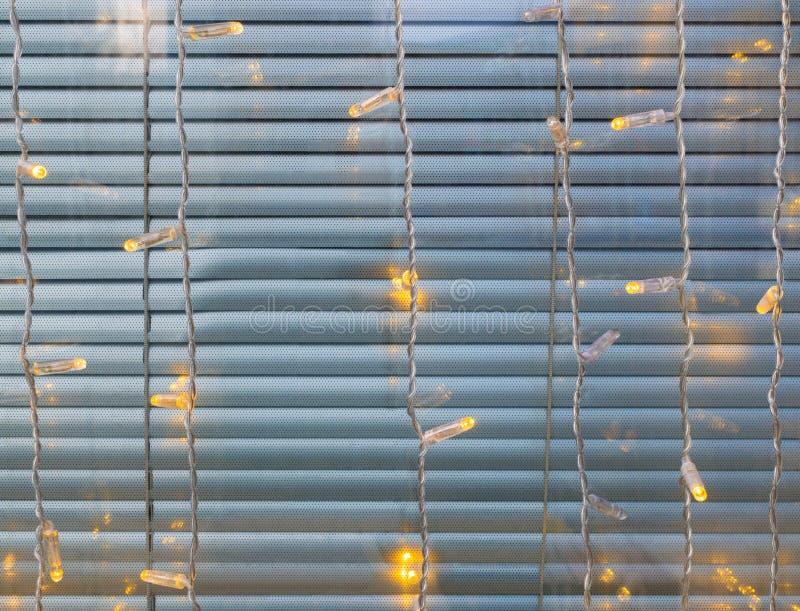 Julbelysning mot fönster royaltyfria bilder