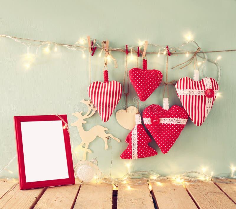 Julbilden av röda hjärtor för tyg och den tomma ramen, girland tänder och att hänga på rep framme av blå träbakgrund fotografering för bildbyråer
