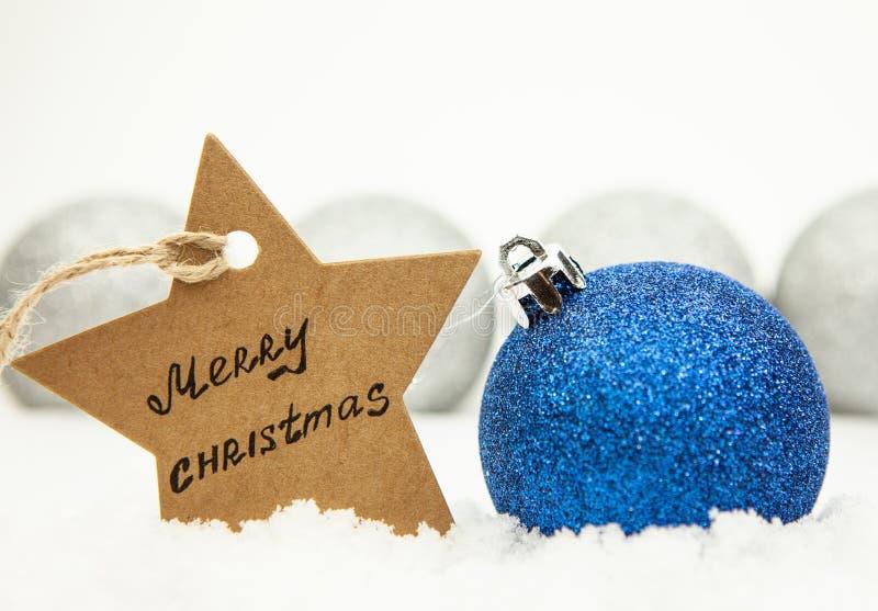 Julboll i blått på vit snö och en stjärna med den glade julen för inskrift, i bakgrundssilverbollarna arkivfoton