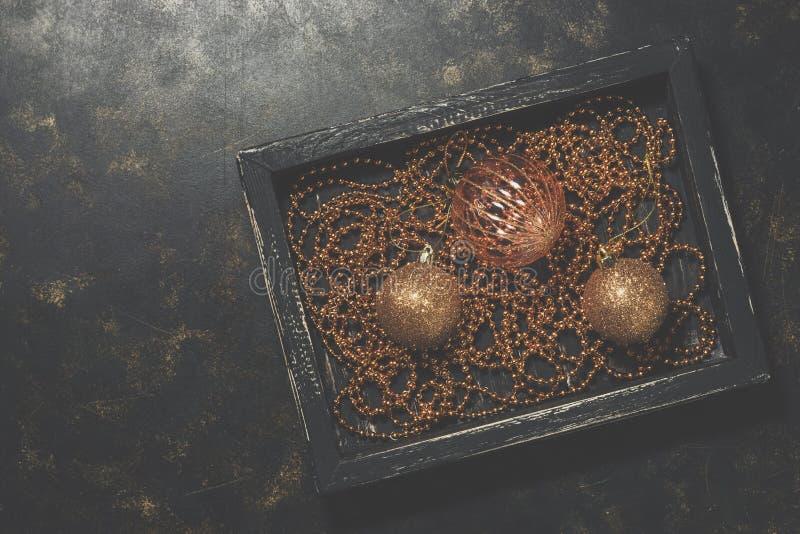Julbollar och pärlor i ett svart trämagasin på en mörk lantlig bakgrund Stilfulla tappningprydnader för guld- jul Top beskådar royaltyfria bilder