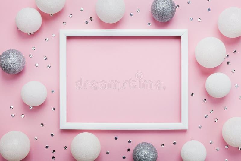 Julbollar, paljetter och bildram på stilfull rosa bästa sikt för tabell skärm för efterföljd för bakgrundsdatormode Lekmanna- läg royaltyfri fotografi