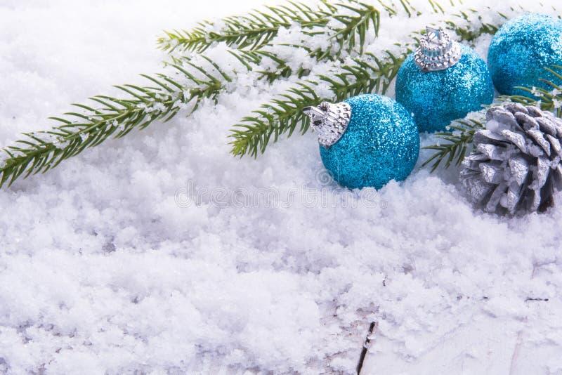 3 julbollar, sörjer kottar och gör grön filialen på snö arkivbild