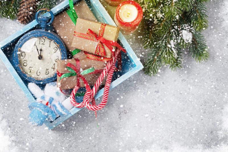 Juldekorask, gåvaaskar, stearinljus och granträdfilial som täckas av snö på stenbakgrund Xmas-bakgrund för bästa sikt med arkivbilder