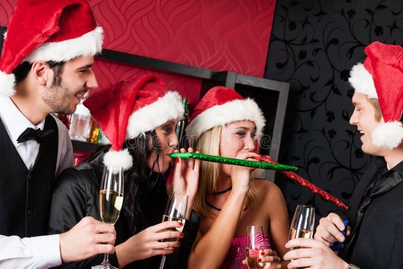 Juldeltagarevänner har gyckel på stången royaltyfri foto