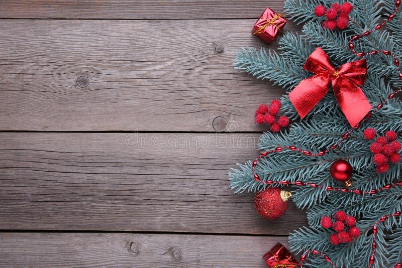 julen dekorerar nya home idéer för garnering till Gran-träd filial med bollar, bulor, bär av viburnumen och gåvor på en grå bakgr royaltyfria foton