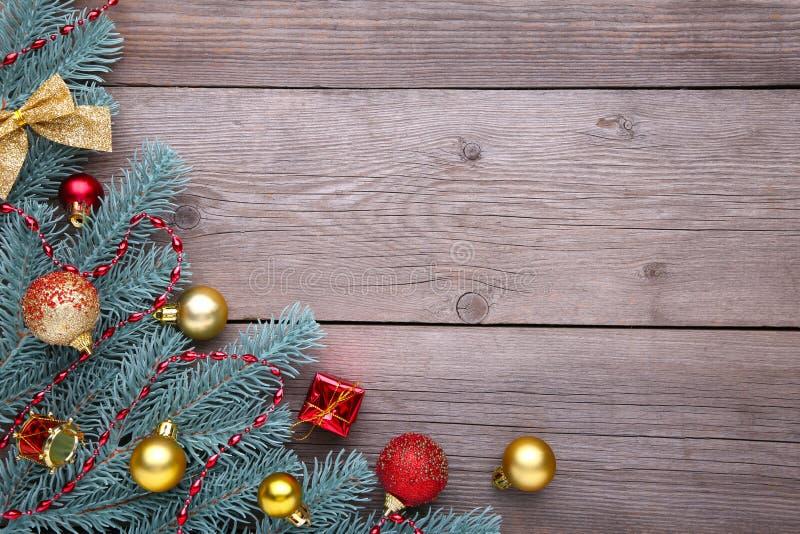 julen dekorerar nya home idéer för garnering till Gran-träd filial med bollar, gåvor och pilbågar på en grå bakgrund royaltyfria foton