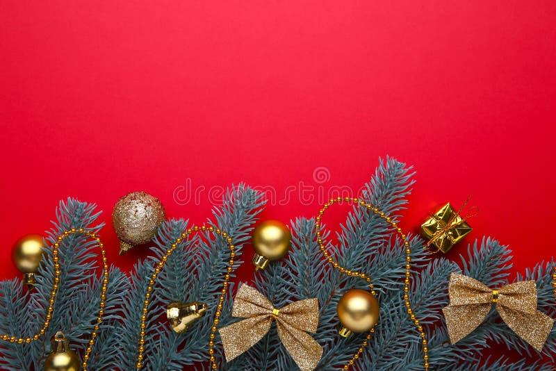 julen dekorerar nya home idéer för garnering till Gran-träd filial med guld- bollar, små gåvor och pilbågar på en röd bakgrund arkivbild