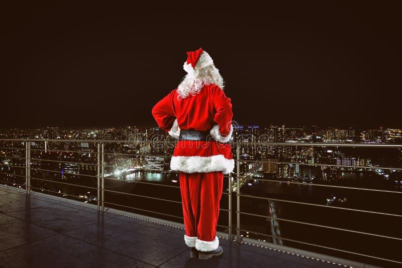 Julen ?r kommande Santa Claus p? en taksiktsstad royaltyfri foto