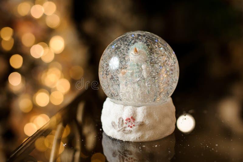 Julexponeringsglasboll med en gullig snögubbeinsida royaltyfria foton