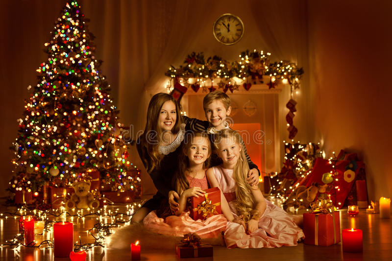 Julfamilj i dekorerat hem- rum, julgranljus arkivfoton