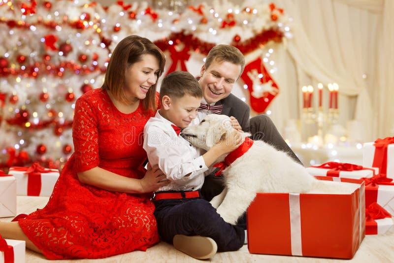Julfamiljen ger hunden den närvarande gåvan som firar lyckligt nytt år arkivfoton