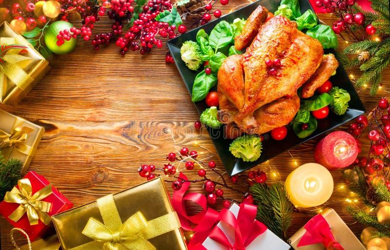 Julfamiljmatställe Grillad höna på ferietabellen som dekoreras med gåvaaskar, brinnande stearinljus och girlander arkivfoton