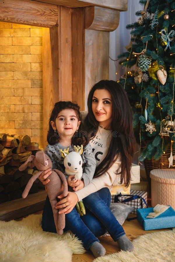 Julfamiljstående av den lyckliga le modern som nära kramar den lilla dottern till julträdet Xmas för vinterferie och nytt år royaltyfria bilder