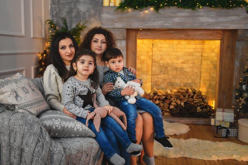 Julfamiljståenden av lyckligt le fostrar att krama deras barn nära till spisen som hemma dekoreras med gran och girlanden arkivfoton