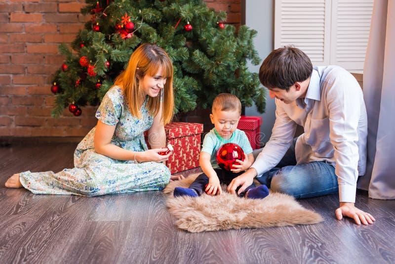 Julfamiljståenden i hem- ferievardagsrum, huset som dekorerar vid Xmas-trädet, undersöker girlanden royaltyfria foton