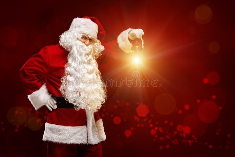 Julfilial och klockor Santa Claus med en lykta i hans hand på ett r royaltyfria bilder