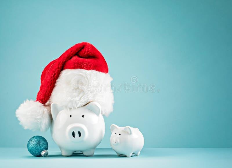 Julfinansspargris som bär den santa hatten royaltyfria bilder