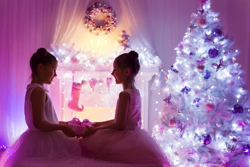 Julflickor, lyckliga barn som ger den närvarande gåvan, Xmas-träd royaltyfri fotografi