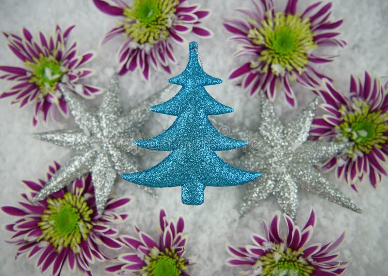 Julfotografibilden av blänker trädet, och stjärnagarneringar med lilagräsplan blommar i insnöat bakgrunden royaltyfria bilder