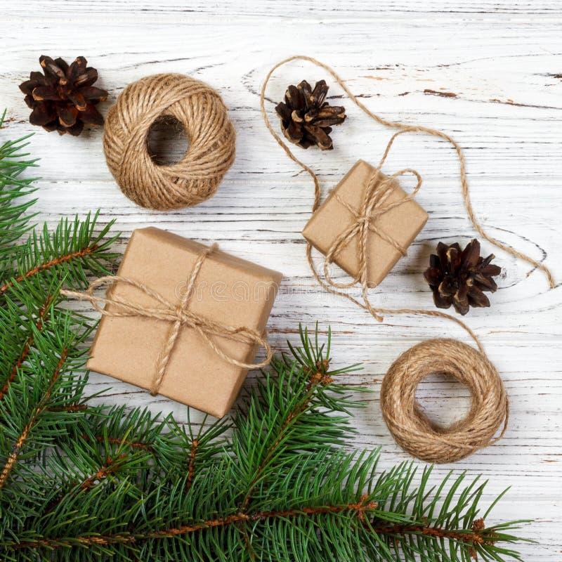 Julgåva eller närvarande ask som slås in i kraft papper med garnering på lantlig träbakgrund arkivfoton