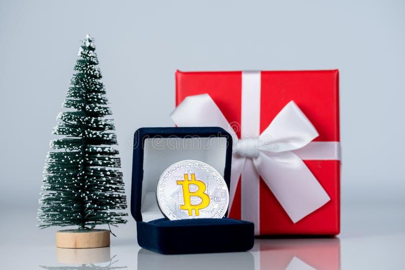 Julgåva eller nytt år med bandet och det lilla bästa gåvabitcoinmyntet för gran och på ljus bakgrund Cryptocurrency royaltyfria bilder
