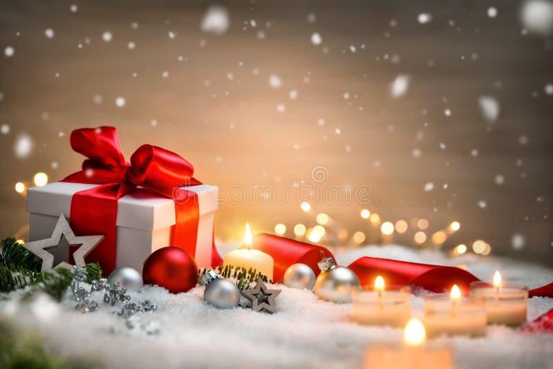 Julgåva med snö, stearinljus och prydnader royaltyfri foto