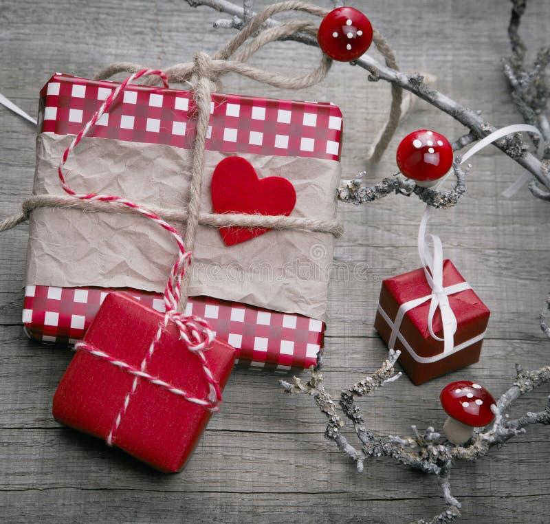 Julgåva som slås in i rött kontrollerat papper - sjaskig stil fotografering för bildbyråer