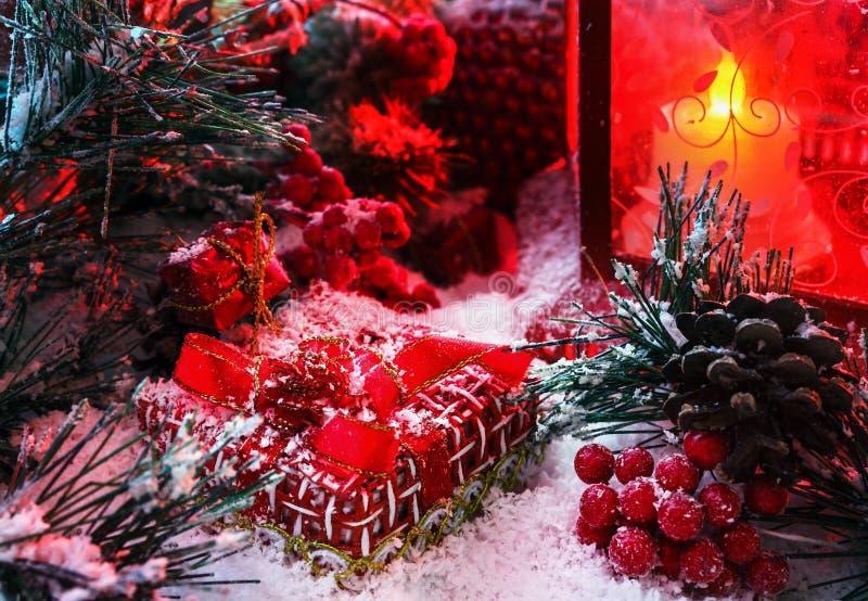 Julgåva som täckas med insnöat ljuset av en röd lykta på bakgrunden av landskap för ` s för nytt år royaltyfria foton