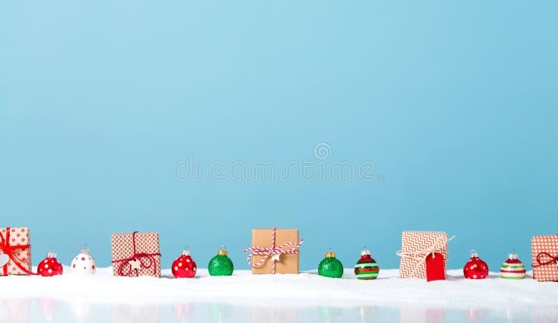 Julgåvaaskar i ett snö täckt landskap arkivbilder