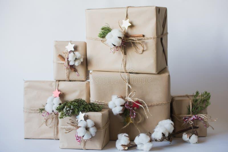 Julgåvaaskar med blommor och dekorativ objektEco bomull, kanel, granfilialer och jute rope härvan över vit backg arkivfoto