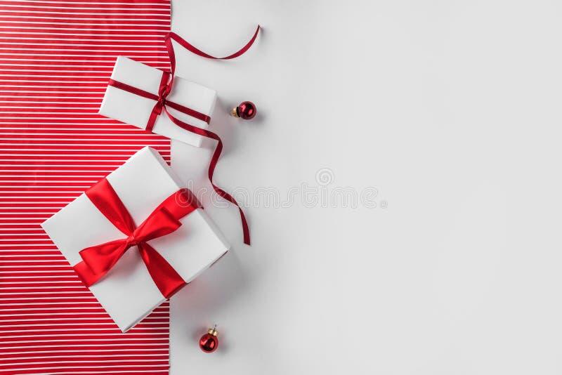 Julgåvaaskar med det röda bandet, garnering på vit och röd pappers- bakgrund royaltyfri bild