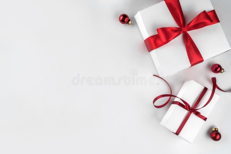Julgåvaaskar med det röda bandet och garnering på vit bakgrund Tema för Xmas och för lyckligt nytt år royaltyfri fotografi