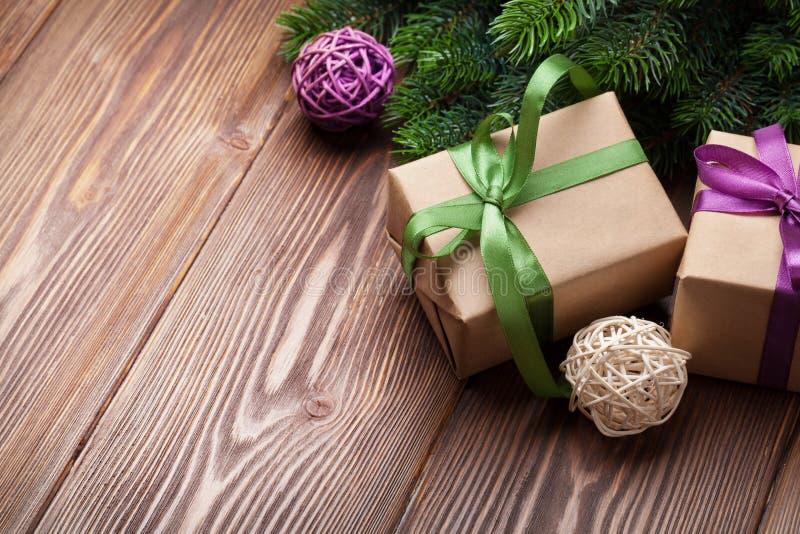 Julgåvaaskar och granträd på tabellen royaltyfria bilder