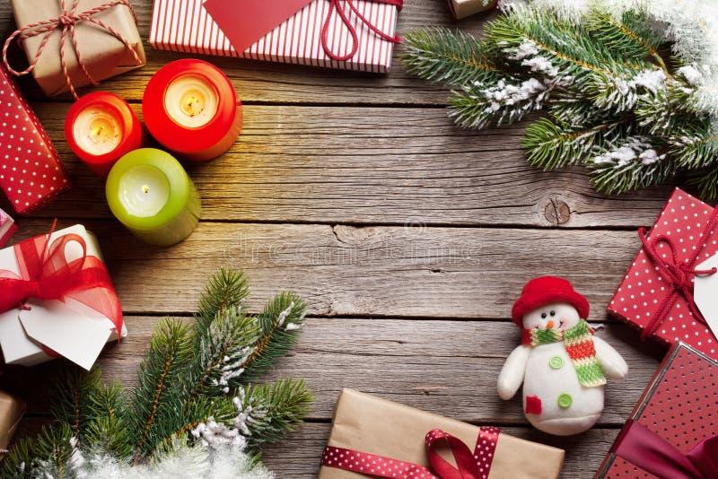 Julgåvaaskar och stearinljus på trätabellen royaltyfri foto