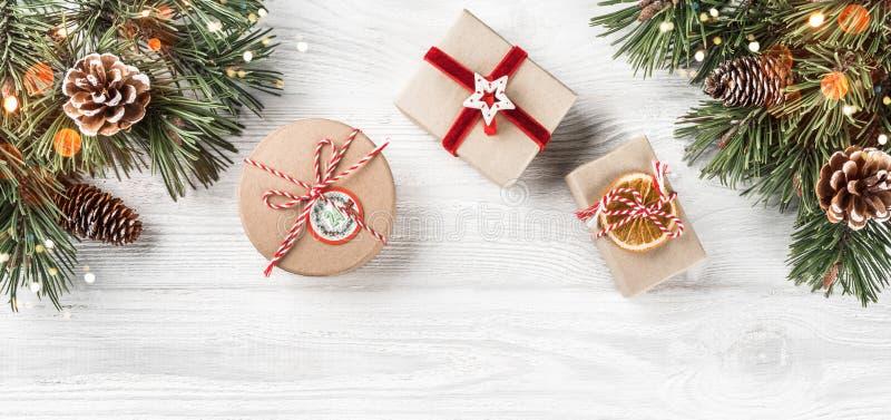 Julgåvaaskar på vit träbakgrund med granfilialer, sörjer kottar Tema för Xmas och för lyckligt nytt år, bokeh som gristrar royaltyfri foto