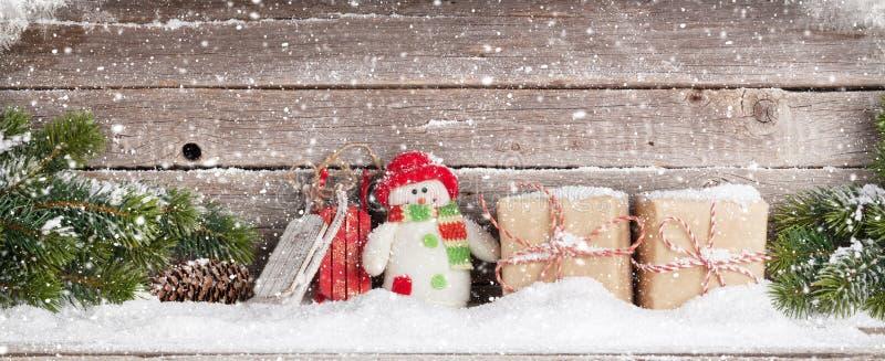 Julgåvaaskar, snögubbeleksak och xmas-granträd arkivfoto