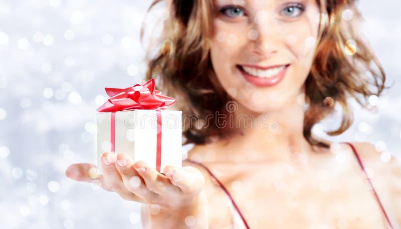 Julgåvagåva, kvinna med packen på suddig ljus lig arkivbild
