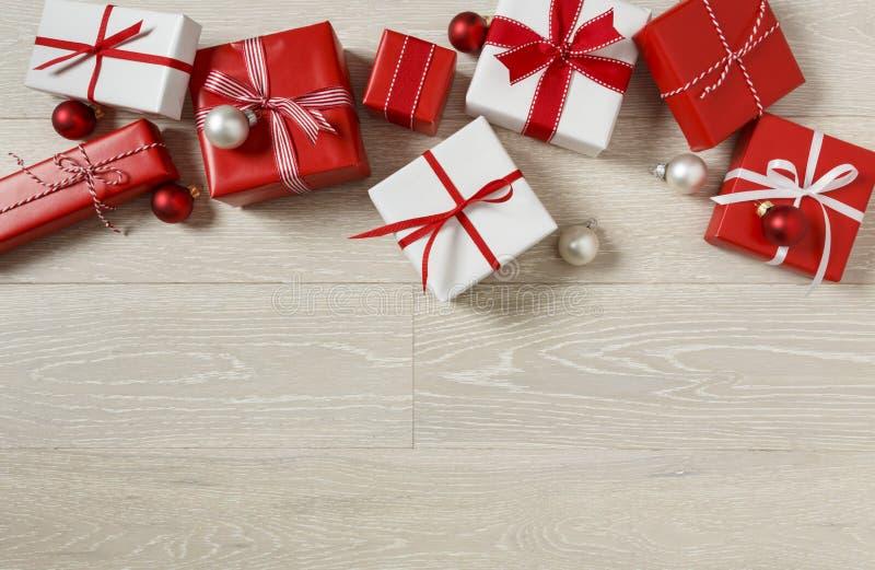 Julgåvagåvor på lantlig wood bakgrund Enkel, röd och vit gräns för ferie för gåvaaskar festlig arkivfoto