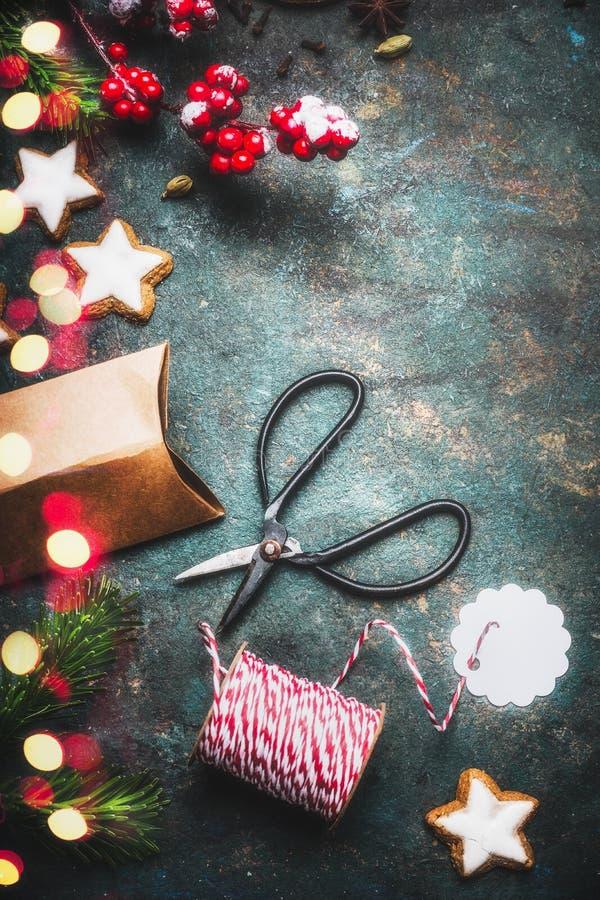 Julgåvainpackning med pappers- askar och band dem upp med det röda repet, gammal sax och röda gröna feriegarneringar, överkant VI arkivfoton