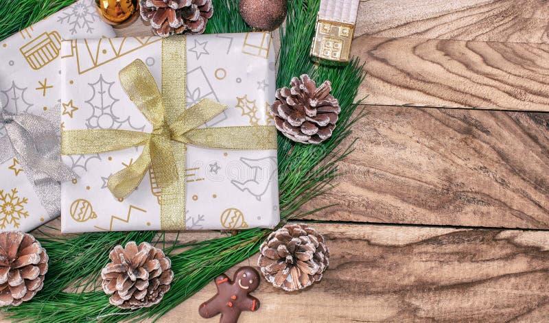Julgåvasjal, gåvapapper, gåvaaskar, granträd, med kottar och garneringar på en träbakgrund med utrymme för fri text royaltyfria bilder