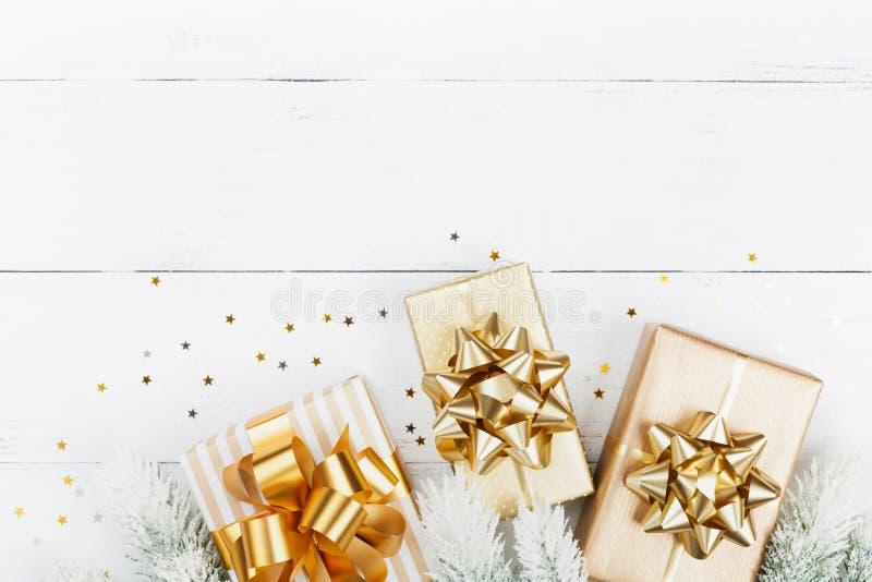 Julgåvor eller gåvaaskar, granträd och stjärnakonfettier på den vita träbästa sikten för tabell Lekmanna- lägenhet arkivfoton