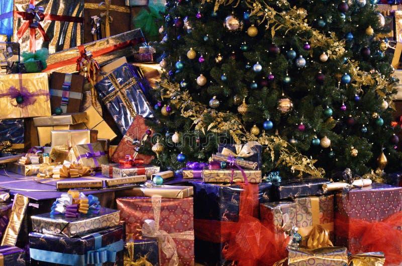 Julgåvor rundar grunden av en julgran royaltyfri bild