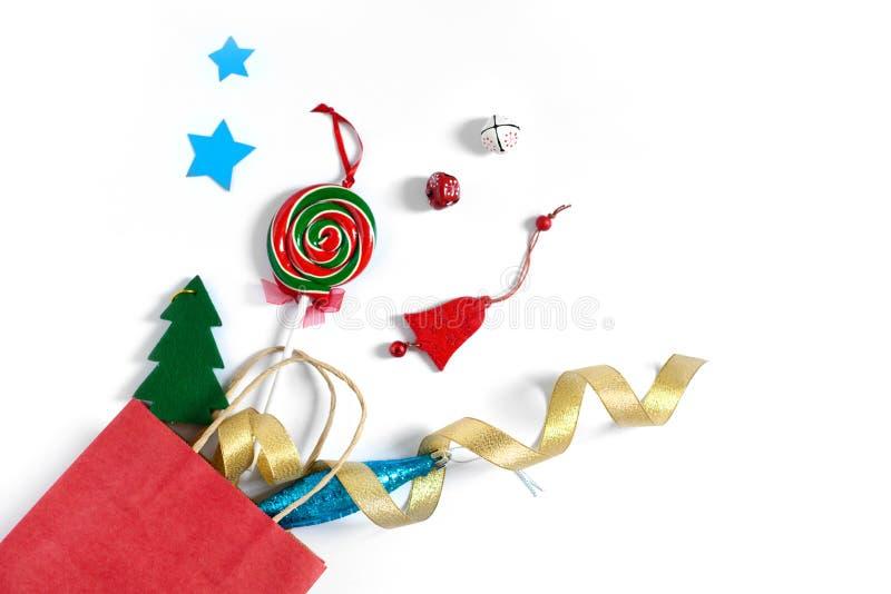 Julgåvor som faller från den röda shoppingpåsen, feriegåvor som isoleras på vit bakgrund, feriebegrepp arkivbilder