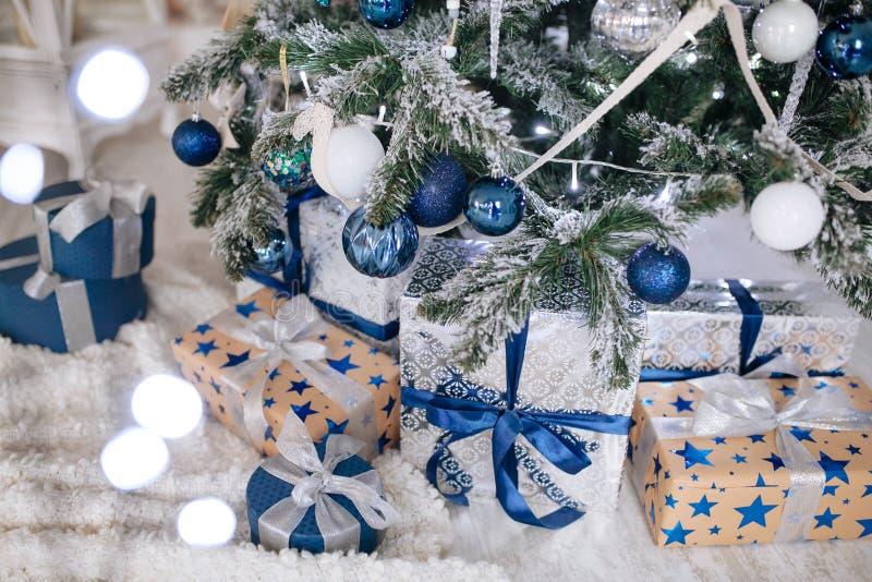 Julgåvor som slås in i silver och blått papper, bakgrund med xmas-ljusbokeh av den suddiga under-julgranen royaltyfri foto