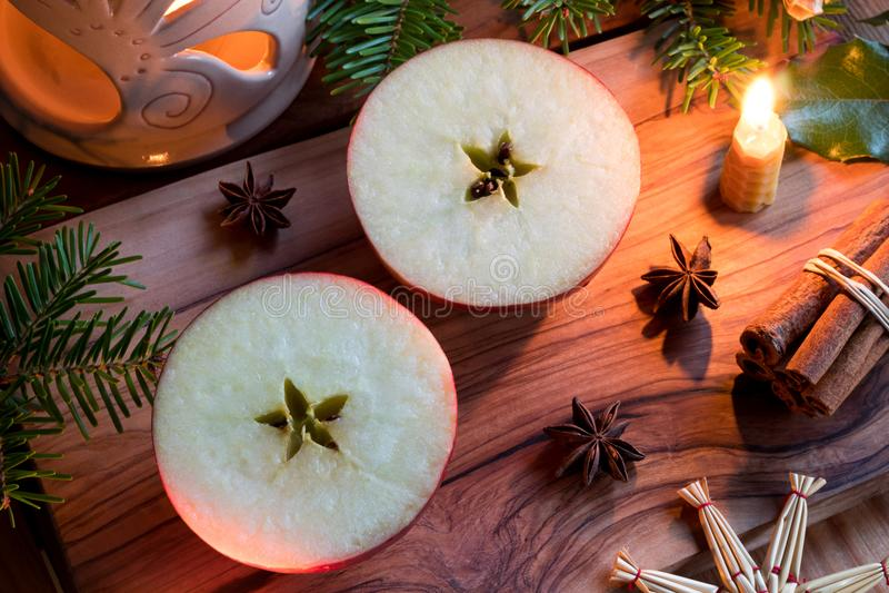Julgarnering - halverat äpple, stearinljus, kanelbruna pinnar, st royaltyfria bilder