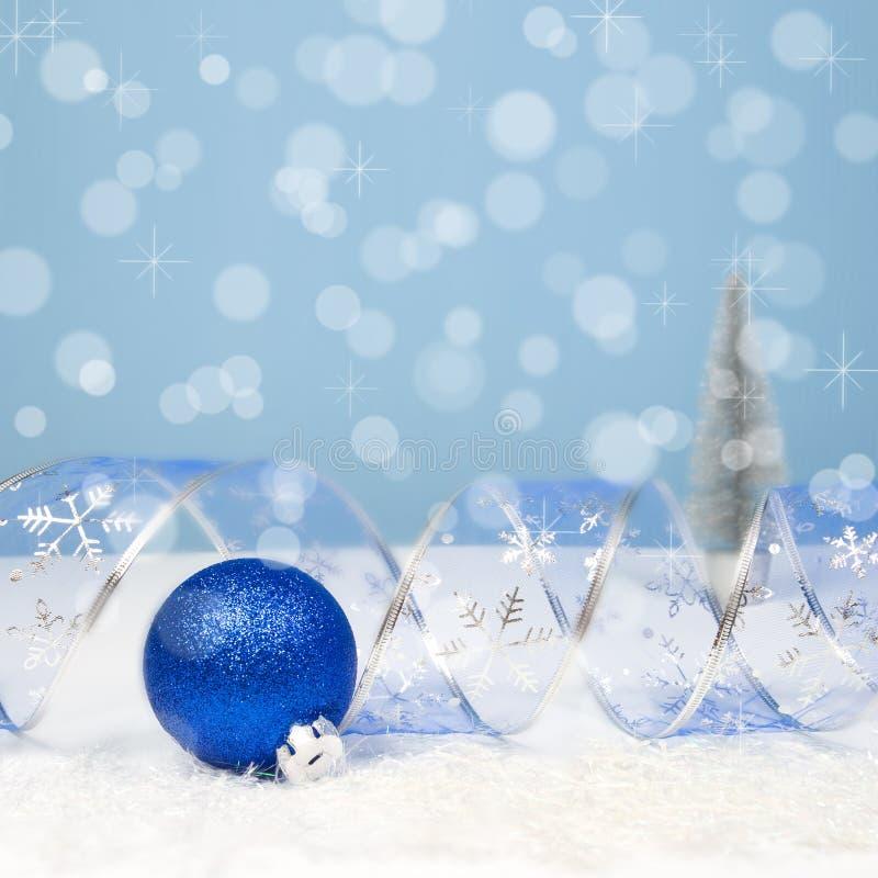 Julgarnering med en blå boll, krökt band på bokehlodisar arkivbilder
