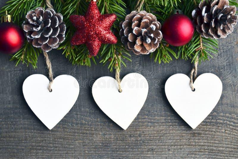 Julgarnering med granträdet, sörjer kottar och vita trähjärtor på gammal träbakgrund arkivfoton