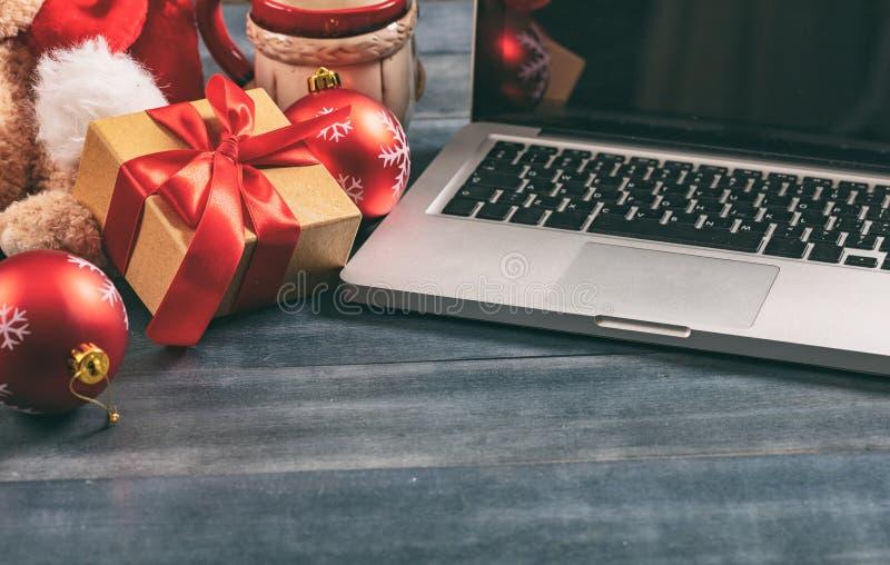 Julgarnering och en datorbärbar dator på ett kontorsskrivbord arkivfoto