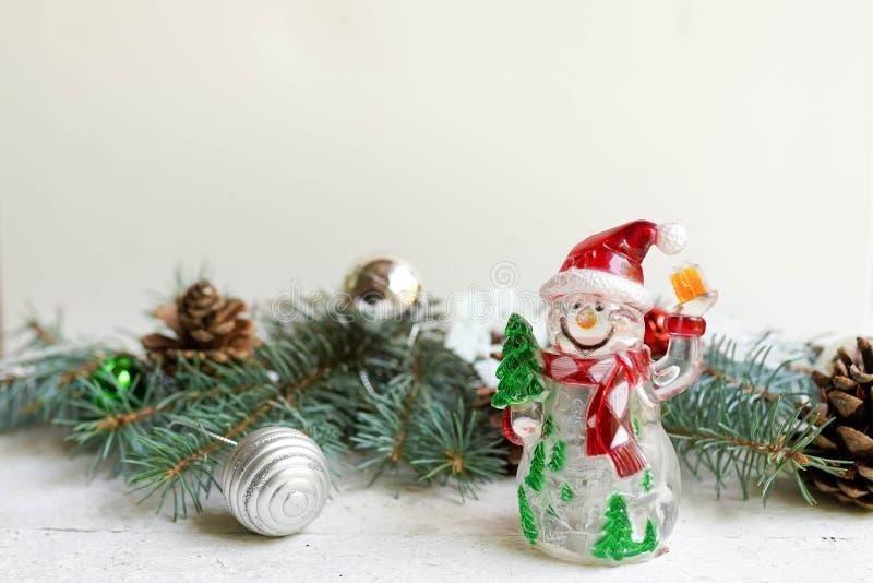 Julgarnering och snögubbe på vit bakgrund med kopieringsutrymme Ber?mh?lsningkort royaltyfria bilder